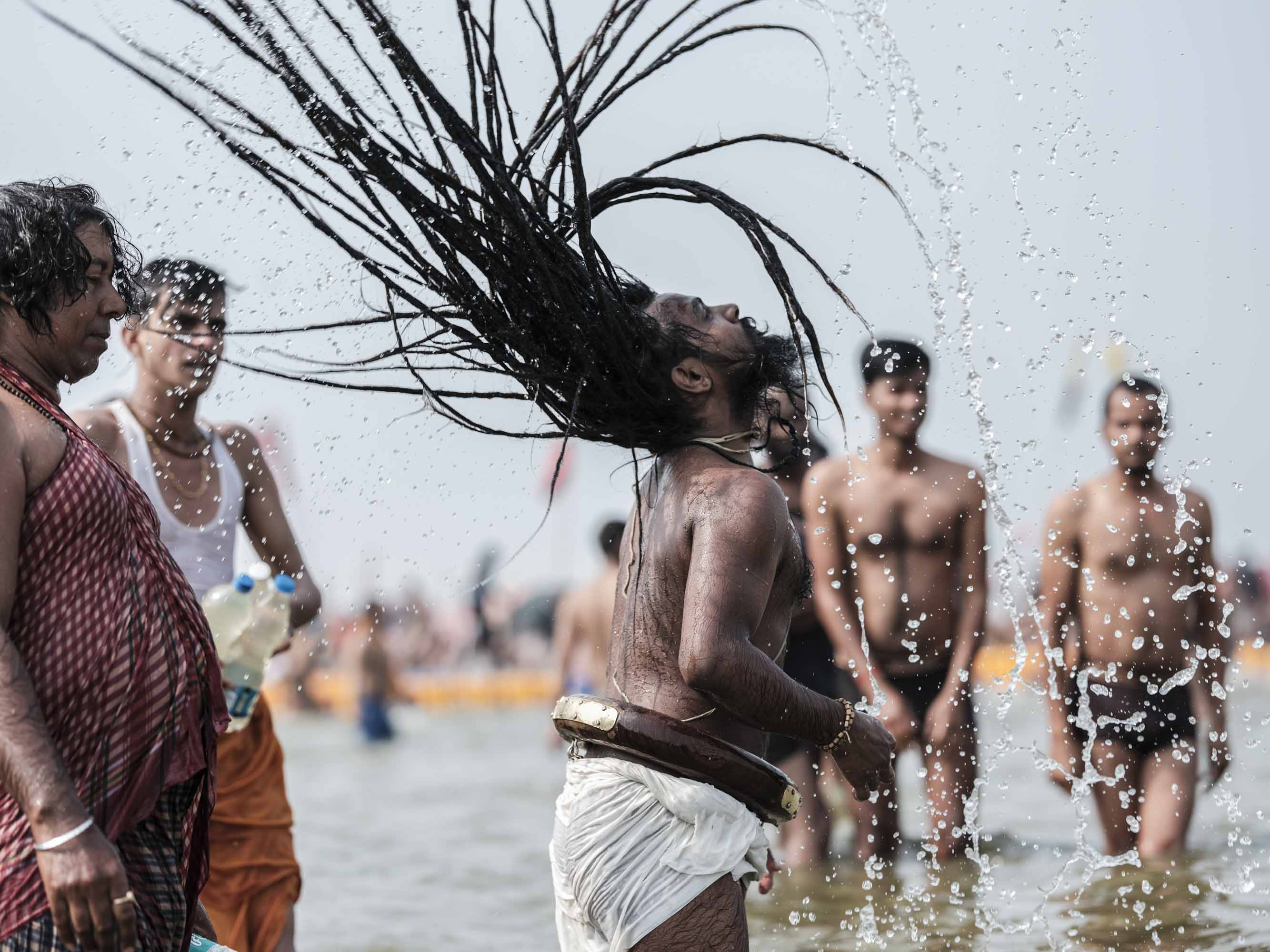 long hair baba rasta water splash pilgrims Kumbh mela 2019 India Allahabad Prayagraj Ardh hindu religious Festival event rivers photographer jose jeuland photography