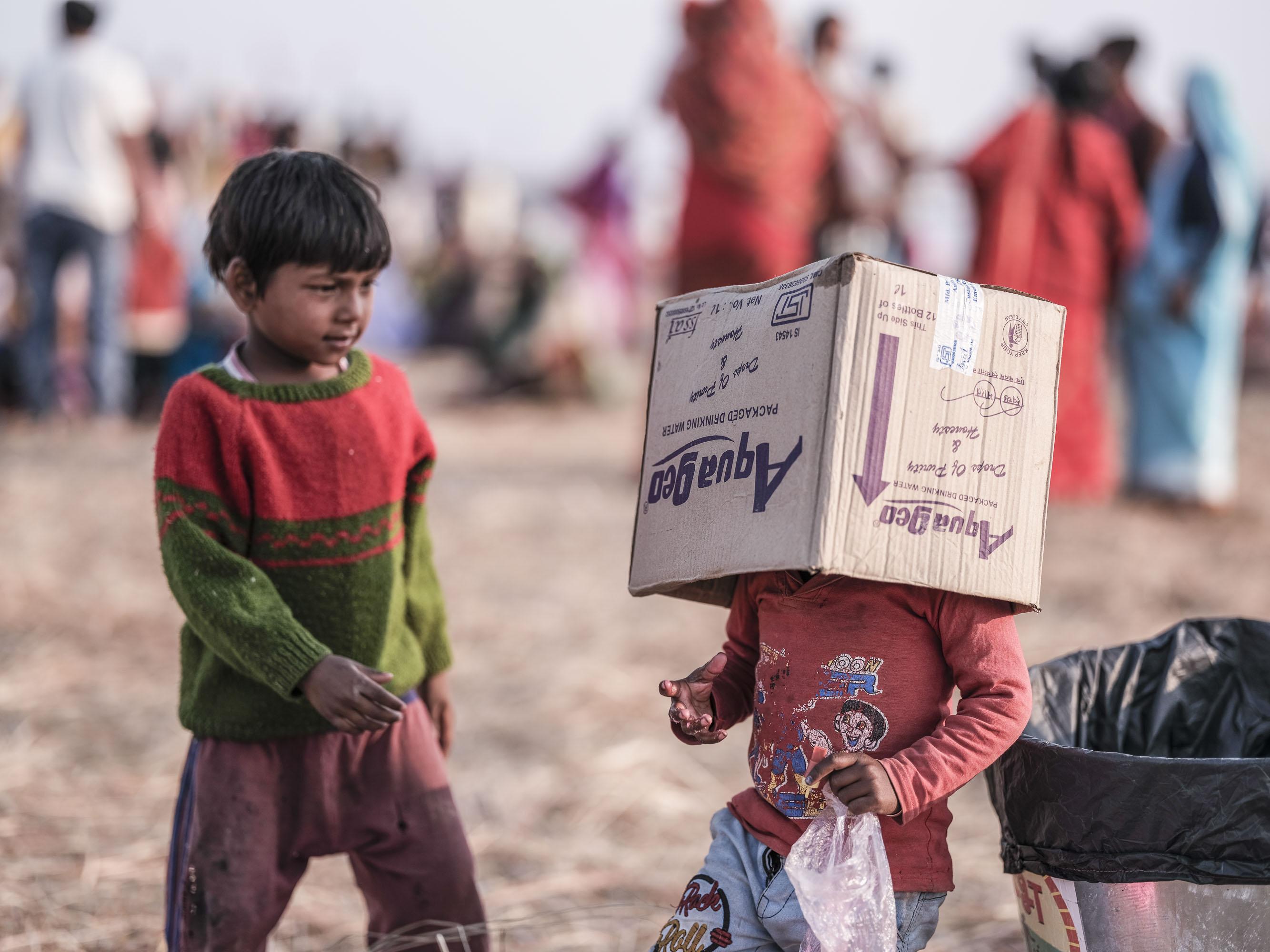 kids playing in the camp with a carton box pilgrims Kumbh mela 2019 India Allahabad Prayagraj Ardh hindu religious Festival event rivers photographer jose jeuland photography